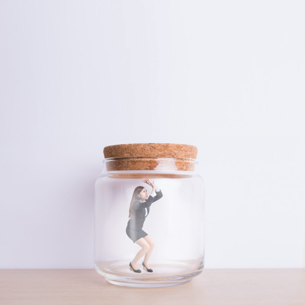 business woman imprisoned in jar with white wall background, great for your design or text, asian