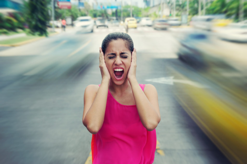 Portrait of woman standing still in the middle of a street with cars passing by fast, screaming stressed and frustrated